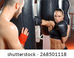 Small photo of Strong jab. Young beautiful woman boxer kicking a punching bag with a jab