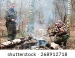 Two Hunters Cooking Dinner Ove...