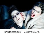 Small photo of Two fashion models fighting backstage. Aggressed woman has bloody eyes.