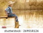 Little Boy Is Fishing At Sunse...