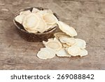 Small photo of Chinese Herbal medicine - American Ginseng slices (Panax quinquefolius) in a bowl on wooden board (manual focus)