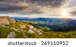 panoramic mountain landscape. valley with stones in grass on top of the hillside of mountain range in sunset light - stock photo