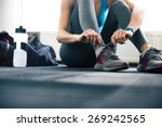 woman tying shoelaces at gym | Shutterstock . vector #269242565