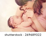 Caring Mother Kissing Little...