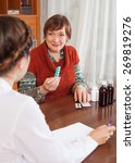 Small photo of sick mature woman complaining to doctor about symptoms of malaise at table