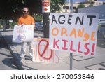 Small photo of Protester against agent orange chemicals holding signs
