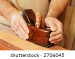 Traditional woodworker using a vintage wooden smoothing plane on a block of mahogany. - stock photo