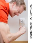 Small photo of Young unreasonable electrocuted man with screwdriver in socket