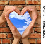 Heart symbol made from hands over a brick with a window into blue sky conceptual photo illustration - stock photo