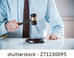 Small photo of Lawyer, judge or auctioneer raising his wooden gavel to pass judgement or knock down a sale to the highest bidder, close up of his hands