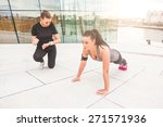 Small photo of Woman doing push-ups exercises with her personal trainer in a modern urban context. She is wearing gray and black sportswear and a phone holder, the trainer look at watch and incite her