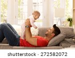 Happy Father Lying On Sofa...