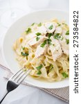 Small photo of Pasta fettuccine alfredo with chicken, parmesan and parsley on white background. Italian cuisine.