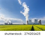 A shiny new lignite power station behind a rye field with wheel tracks leading to it and an old power station in the background - stock photo