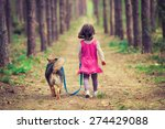 Stock photo little girl walking with dog in the forest back to camera 274429088