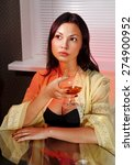 Small photo of beautiful ladylove in dress on sofa with glass of brandy