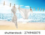 Stock photo decoration of white bikini on rope and sand space 274940075