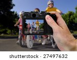 Hand holding camera taking a picture of little girls riding bikes - stock photo