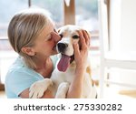 Stock photo senior woman with her dog inside of her house 275330282
