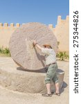 Small photo of Taroudant, Morocco - tourists pose with old quern in front of historic ramparts