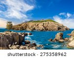 fairytale composite of rocky shore and island with hills and castle with red roofs - stock photo