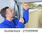 man installing a garage door | Shutterstock . vector #275509898