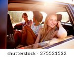 Three Women Sitting In Rear Seat Of Car On Road Trip - stock photo