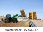 A Farmer Loads A Flat Bed Semi...