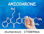 Small photo of Hand with pen drawing the chemical formula of Amiodarone