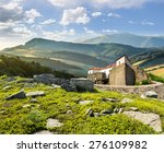 composite mountain landscape with ancient fortress with high stone walls and red roof among the woods and huge boulders on a hillside - stock photo
