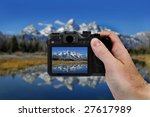 Hand holding camera taking a picture of Teton Mountains and River - stock photo