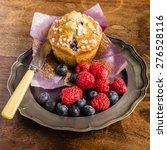 Small photo of Blueberry Muffin arranged on a pewter plate with raspberries and blueberries on a rustic distressed tabletop.