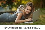 Stock photo beautiful girl with her kitty and laptop outdoors 276554672