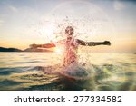 Stock photo man splashing water during summer holidays young attractive man having fun on a tropical beach at 277334582
