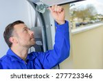 man installing a garage door | Shutterstock . vector #277723346