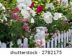 Stock photo flowers spilling over white picket fence 2782175