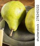 Small photo of Fresh green pears on a pewter plate with a vintage knife, placed on a distressed wood table, photographed from above. Close up.