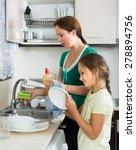 Girl Helping Mother Washing...