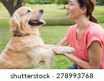 Stock photo pretty brunette playing with her dog in the park on a sunny day 278993768