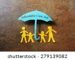 Small photo of Paper family of four under a Affordable Care Act umbrella