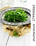Small photo of Fresh rocket leaf salad on an antique pewter plate on hessian fabric in a rustic setting against a light, bright background. Concept image for healthy eating. Copy space.