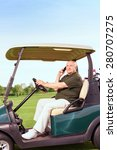 Small photo of Looking busy. Portrait of senior man sidewise using mobile phone and driving cart on course.
