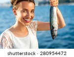 Young Woman Holding Fresh Fish...
