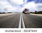 Roadtrain in Nullarbor desert,Australia. At left side sign with quarantine restrictions. - stock photo