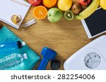 Stock photo fitness and weight loss concept dumbbells white scale towels fruit tape measure and digital 282254006