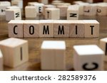 Small photo of commit word written on wood block