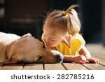 Stock photo a portrait of a little cute toddler girl kissing her dog a yellow labrador relaxing on the wooden 282785216