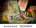 Small photo of A pile of tarot trump cards jumbled, scattered and haphazardly arranged.