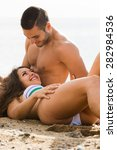 happy couple  on sand beach at... | Shutterstock . vector #282984536