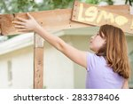 Young girl painting lemonade stand places her hand, covered in yellow paint, on the sign to make a hand print. - stock photo